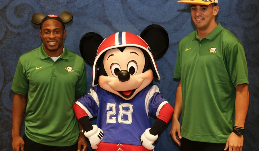 Oregon defensive back Ifo Ekpre-Olomu, left, and Oregon quarterback Marcus Mariota, right, pose for a photo with Mickey Mouse during a media availability prior to the College Football Awards, Wednesday, Dec. 10, 2014, at Disney World in Lake Buena Vista, Fla. The College Football Awards will be held on Thursday evening. (AP Photo/John Raoux)