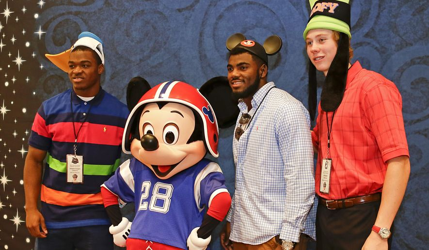 Alabama players, from left, receiver Amari Cooper, defensive back Landon Collins and punter JK Scott, pose for a photo with Mickey Mouse during a media availability prior to the College Football Awards, Wednesday, Dec. 10, 2014, at Disney World in Lake Buena Vista, Fla. The College Football Awards will be held on Thursday evening. (AP Photo/John Raoux) **FILE**