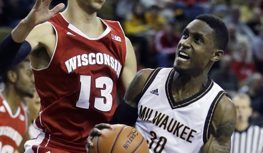 Wisconsin-Milwaukee's JeVon Lyle tries to drive past Wisconsin's Duje Dukan (13) during the second half of an NCAA college basketball game Wednesday, Dec. 10, 2014, in Milwaukee. (AP Photo/Morry Gash)