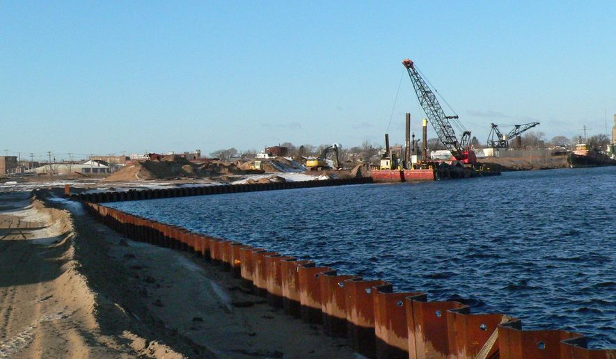 In a Dec. 1, 2014 photo shows the progress of the dredging on the north shore of Escanaba, Mich.. Basic Marine has begun the development of Escanaba's north shore, which will become the home of a new deep water port. For a fully-loaded carrier to dock, the lake bottom needed to be dredged to around 26 feet. (AP Photo/Daily Press of Escanaba, Ilsa Matthes)