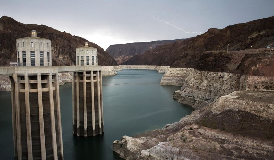FILE - In this July 28, 2014 file photo, lightning strikes over Lake Mead near Hoover Dam at the Lake Mead National Recreation Area, near Boulder City, Nev.  The bathtub ring of light minerals shows the high water mark of the reservoir which has shrunk to its lowest point since it was first filled in the 1930s. Amid worries that crucial multi-state water agreements are beginning to erode due to ongoing drought, representatives of seven Colorado River basin states are meeting in Las Vegas this week. Colorado Gov. John Hickenlooper is set to get a report Wednesday, Dec. 10, 2014, calling for his state to capture and use every legal drop of Rocky Mountain snowmelt before it flows downstream. Meanwhile, officials from Arizona, California and Nevada are touting a cooperative agreement aimed at keeping the water level above critical stage at drought-depleted Lake Mead. The federal Bureau of Reclamation is also involved. (AP Photo/John Locher, File)