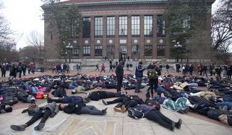 University of Michigan students lay on the ground during a protest of the killing of unarmed black men by white police, at the University of Michigan in Ann Arbor, Mich., on Wednesday, Dec. 10, 2014. (AP Photo/The Ann Arbor News, Patrick Record)