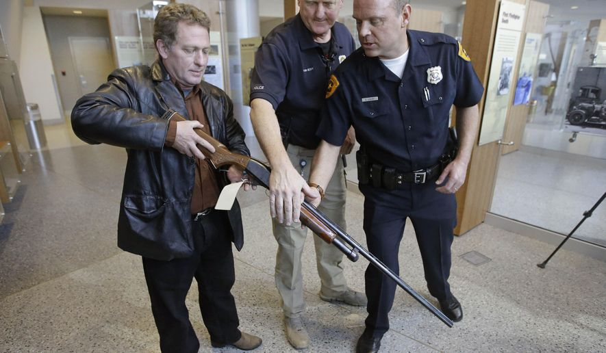 Richard Pittenger, the Utah man who filed a stolen property report on his 20-gauge shotgun 37 years ago, stands holding it with Salt Lake City Police Detectives Rod Van Scoy, center and  Cody Lougy, right, after it was returned at the Public Safety Building Wednesday, Dec. 10, 2014, in Salt Lake City. Pittenger was in high school when the gun he used to hunt with his father was stolen from his truck during a break-in in 1977. Now, decades later, the 20-gauge shotgun turned up in Oregon, where a serial number search connected it to Pittenger's long-ago report. (AP Photo/Rick Bowmer)