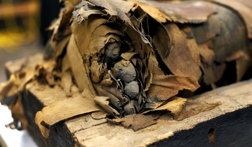 FILE- In this Dec. 5, 2014, photo,  the mummified body of Minirdis, a 14-year-old Egyptian boy and his exposed toes lie in his opened coffin after J.P. Brown and his team of curators at the Field Museum opened the coffin for the first time in Chicago. The team opened the coffin of the 2,500-year-old mummy to perform conservation work before it becomes part of a traveling exhibition. (AP Photo/Charles Rex Arbogast, File)