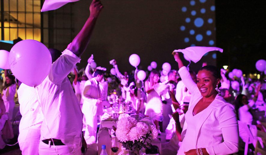 "People wave white napkins in the air during the ""Diner en Blanc"" event at SoundScape Park, Tuesday, Dec. 9, 2014, in Miami Beach, Fla. About a thousand people gathered at the pop-up picnic event that started in Paris in 1988 and has spread worldwide. Invitations are spread by word of mouth and the location of the dinner is kept secret until the last minute. (AP Photo/Lynne Sladky)"