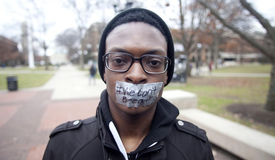 "University of Michigan sophomore Travis Jones III, 19, stands with his mouth taped shut with ""#We Can't Breathe"" written on the tape during a protest of the killing of unarmed black men by white police, at the University of Michigan in Ann Arbor, Mich., on Wednesday, Dec. 10, 2014. (AP Photo/The Ann Arbor News, Patrick Record)"