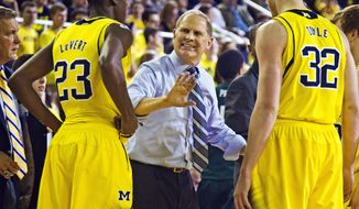 Michigan head coach John Beilein, center, gives instructions to guard Caris LeVert (23) and forward Ricky Doyle (32) during a timeout in the second half of an NCAA college basketball game against Eastern Michigan at Crisler Center in Ann Arbor, Mich., Tuesday, Dec. 9, 2014. Eastern Michigan won 45-42. (AP Photo/Tony Ding)