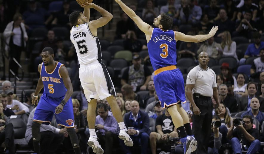 San Antonio Spurs' Cory Joseph (5) shoots over New York Knicks' Jose Calderon (3) during the first half of an NBA basketball game, Wednesday, Dec. 10, 2014, in San Antonio. (AP Photo/Eric Gay)