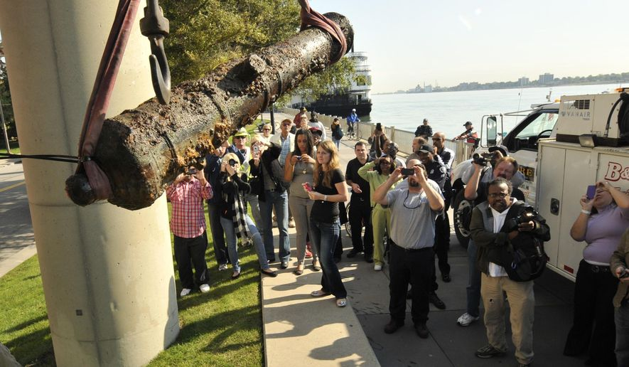 FILE- In an Oct. 5, 2011 file photo, a large crowd photographs the last of five sunken cannons believed to be over 200 years old recovered from the Detroit River in Detroit. The 18th century British cannon that was found in the Detroit River by police divers taking part in training is going on display this weekend following a three-year restoration.  An event is planned Wednesday, Dec. 10, 2014 where the cannon will be shown to media. It will be displayed at the Dossin Great Lakes Museum on Belle Isle. (AP Photo/The Detroit News, Max Ortiz)  DETROIT FREE PRESS OUT