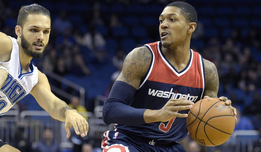 Washington Wizards guard Bradley Beal, right, drives past Orlando Magic guard Evan Fournier, of France, during the first half of an NBA basketball game in Orlando, Fla., Wednesday, Dec. 10, 2014. (AP Photo/Phelan M. Ebenhack)