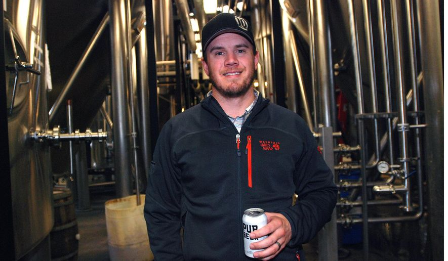 In this Nov. 18, 2014 photo, 10 Barrel Brewing Co. partner Garrett Wales poses in the company's brewery, in Bend, Ore. As it grew from a struggling timber town to an outdoor recreation destination, Bend, Ore., has seen an explosion of breweries, making it one of the top beer towns in the country. When 10 Barrel announced it was being bought by the world's biggest brewer, Anheuser-Busch Inbev, many local beer lovers felt betrayed. (AP Photo/Jeff Barnard)