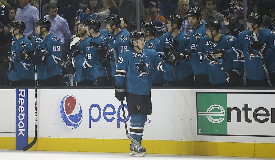 San Jose Sharks center Logan Couture (39) celebrates with teammates on the bench after scoring a goal against the Edmonton Oilers during the second period of an NHL hockey game Tuesday, Dec. 9, 2014, in San Jose, Calif. (AP Photo/Tony Avelar)
