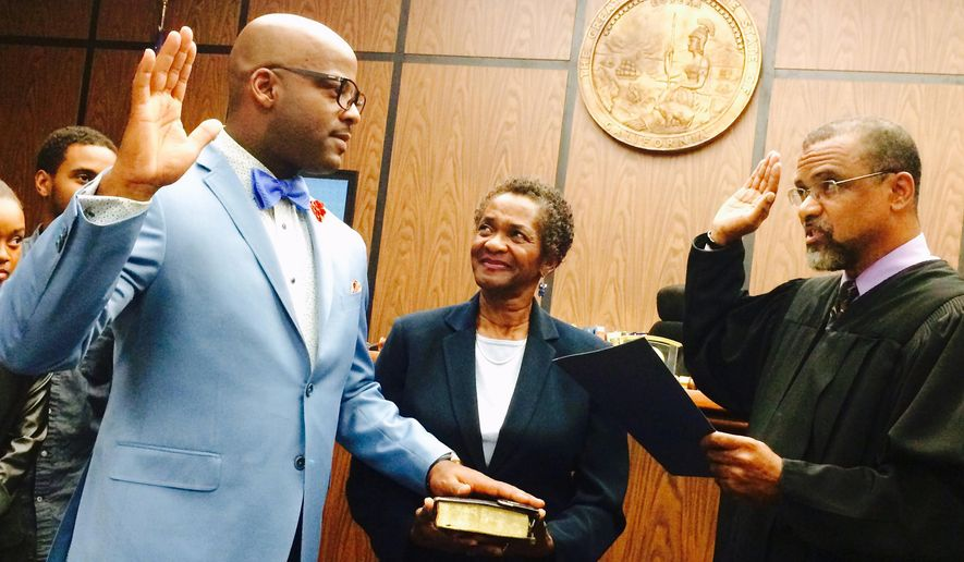 In this photo provided by the office of state Sen. Isadore Hall, Superior Court Judge Kelvin Filer, right swears in state Sen. Isadore Hall, left, while Hall's mother Dorothy Vann, center, looks on at the Compton Superior Court, Wednesday, Dec. 10, 2014, in Compton, Calif.  The Former state Assemblyman won a special election to replace state Sen. Rod Wright, who resigned in September after being sentenced for lying about where he lived when he ran for office. (AP Photo/Office of Sen. Isadore Hall)