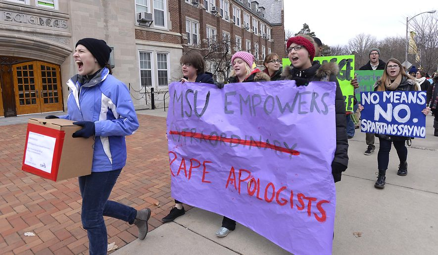 Protesters opposed to the upcoming speech by controversial columnist George Will march through campus in East Lansing, Mich. on Wednesday, Dec. 10, 2014. The group took boxes of petitions opposing Will's visit to the office of MSU President Lou Anna Simon. (AP Photo/Lansing State Journal, Rod Sanford)