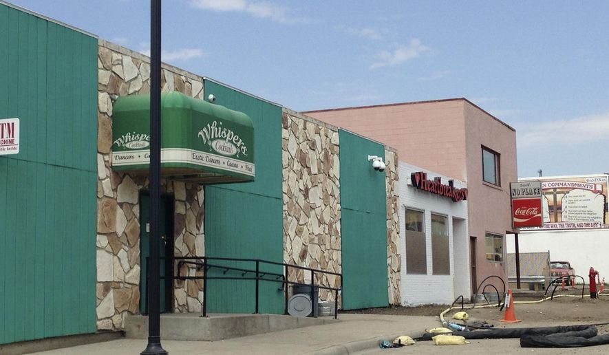 FILE - This Aug. 11, 2014 file photo shows two strip clubs along Main Street in Williston, N.D. Williston commissioners voted unanimously Tuesday night, Dec. 9, 2014, to suspend the liquor licenses of the city's two strip clubs for the second time in two years due to what police say are an excessive number of complaints about disorderly behavior. (AP Photo/Josh Wood, File)