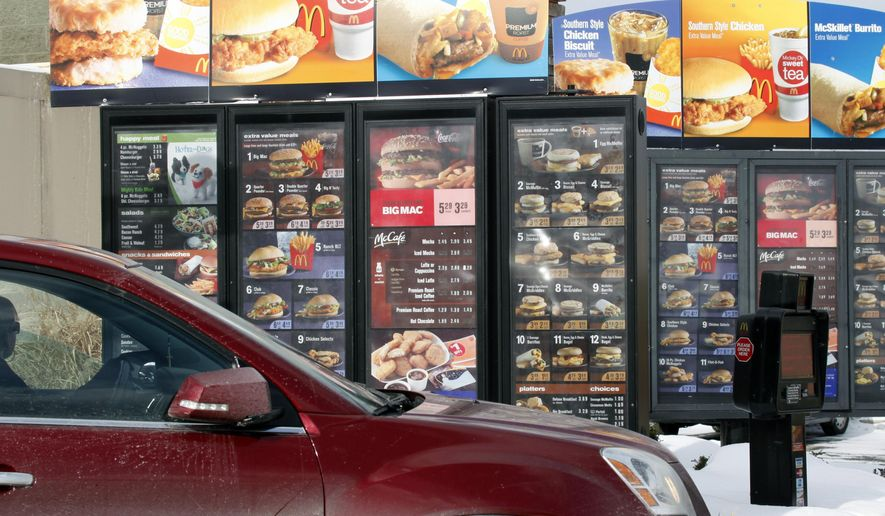 FILE - In this Jan. 26, 2009 file photo, a customer looks at the menu at McDonald's drive-thru in Williamsville, N.Y. McDonald's is planning to trim its menu, review its cooking methods and maybe even get rid of some of the ingredients it uses to change perceptions that it serves junk food, CEO Don Thompson said Wednesday, Dec. 10, 2014. (AP Photo/David Duprey, File)