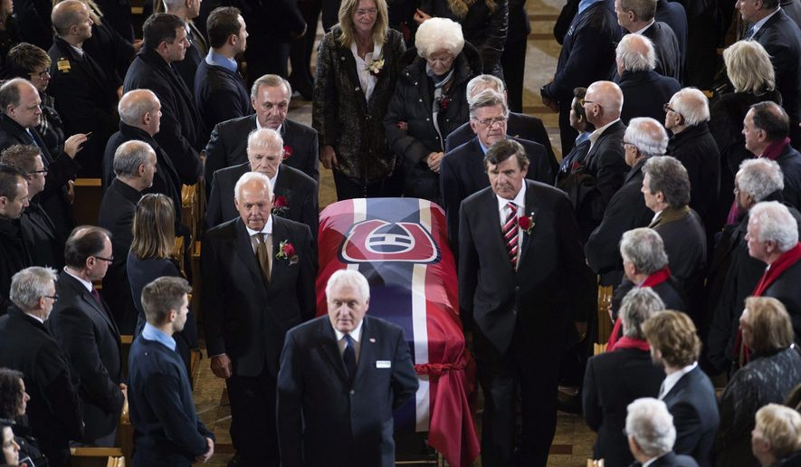 Pallbearers carry the casket as family members walk behind after the funeral service for Montreal Canadiens legend Jean Beliveau Wednesday, Dec.10, 2014 in Montreal.  The widow Elise Beliveau is at center right, and daughter Elise is center left.(AP Photo/The Canadian Press, Paul Chiasson)