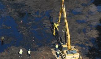 FILE - In this Aug. 6, 2010 file photo workers drain oil near a oil spill by Talmadge Creek in Fredonia Towship, Mich. Enbridge Inc., based in Calgary, Alberta, has agreed to pay about $6.8 million to settle a class-action lawsuit in one of the costliest onshore oil spills in U.S. history. (AP Photo/The Enquirer, John Grap, File)
