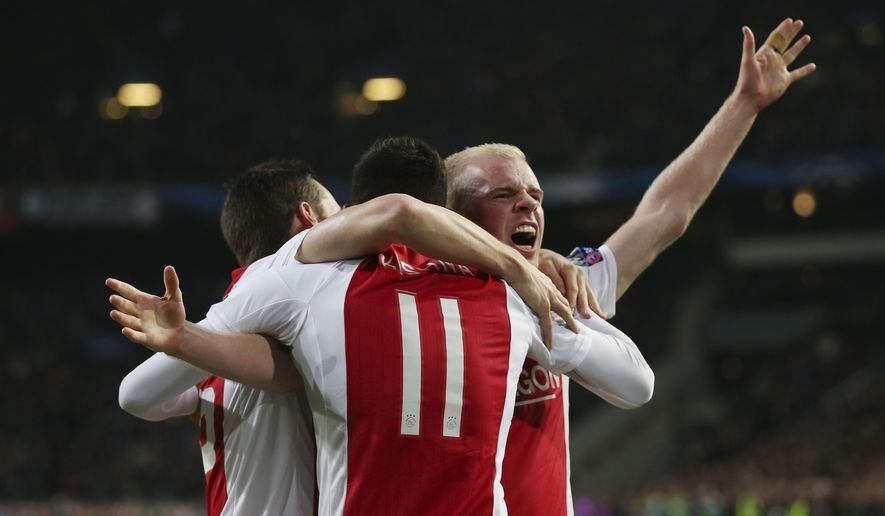 Ajax's Davy Klaassen, right, celebrates with his teammate Ricardo Kishna after scoring the third goal for his team during the Group F Champions League match between Ajax and Apoel at ArenA stadium in Amsterdam, Netherlands, Wednesday, Dec. 10, 2014. (AP Photo/Peter Dejong)