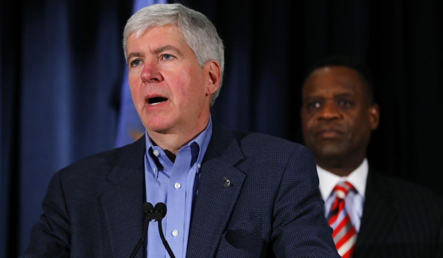 Gov. Rick Snyder, left, speaks as emergency manager, Kevyn Orr listens at a news conference in Detroit Wednesday, Dec. 10, 2014. Snyder said that the nation's largest municipal bankruptcy will end at midnight.  (AP Photo/Paul Sancya)