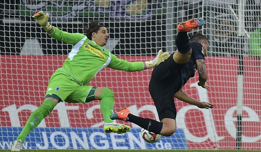 Berlin's Julian Schieber, right, scores against Moenchengladbach's goalkeeper Yann Sommer from Switzerland during the German Bundesliga soccer match between Borussia Moenchengladbach and Hertha BSC Berlin in Moenchengladbach,  Germany, Saturday, Dec. 6, 2014. (AP Photo/Martin Meissner)