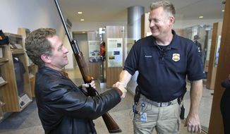 Richard Pittenger, a Utah man who filed a stolen property report on his 20-gauge shotgun 37 years ago, shakes hands with Salt Lake City Police Detective Rod Van Scoy after it was returned at the Public Safety Building Wednesday, Dec. 10, 2014, in Salt Lake City. Pittenger was in high school when the gun he used to hunt with his father was stolen from his truck during a break-in in 1977. Now, decades later, the 20-gauge shotgun turned up in Oregon, where a serial number search connected it to Pittenger's long-ago report. (AP Photo/Rick Bowmer)