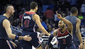 Washington Wizards guard John Wall (2) celebrates with Marcin Gortat, left, and Kris Humphries (43) after teammate Bradley Beal tipped in the game-winning basket as time expired at the end of the second half of an NBA basketball game against the Orlando Magic in Orlando, Fla., Wednesday, Dec. 10, 2014. The Wizards won 91-89. (AP Photo/Phelan M. Ebenhack)