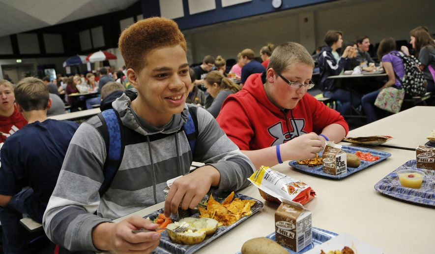ADVANCE FOR WEEKEND -  Takao Douthard talks with friends during lunch on Nov. 6, 2014, at Seeger High School near West Lebanon, Ind. . Being one of the few minority students in the school, Douthard said he is still adjusting. But he added that everyone was very welcoming to him. Public schools in the US began the 2014-15 school year with an unprecedented demographic profile. For the first time, white students are in the minority. (AP Photo/Journal & Courier, John Terhune)