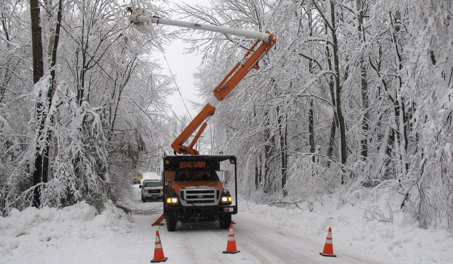 Green Mountain Power cuts limbs overhanging powerline in Waterbury, Vt., on Thursday, Dec. 11, 2014. Tens of thousands of electric customers across Vermont were left in the dark in the aftermath of two-days of heavy, wet snow. GMP says it's the greatest challenge since Tropical Storm Irene of 2011.