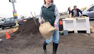 Cat Kaufman brings over a sand bag to protect her South A Street business, Wednesday Dec. 10, 2014 in Santa Rosa, Calif. Northern California residents are bracing for a powerful storm that could be the biggest in five years and which prompted the National Weather Service to issue a high wind and flash flood warning. The storm is expected to arrive Wednesday and pelt the region through Thursday.  (AP Photo/The Press Democrat, Kent Porter)