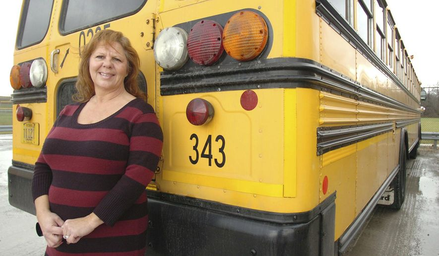 ADVANCE FOR MONDAY DEC. 15 AND THEREAFTER - In a Nov. 24, 2014 photo, Rhonda Rayford poses for a photo with a school bus like the one she drives in Fort Wayne, Ind. When things get too quiet on Rayford's bus, she tells her young riders to start making some noise. The bus ride to and from school is the time to let off steam, and if her kids aren't singing and carrying on, then it's not good, said Rayford, who goes by Miss Rhonda when she is driving.  (AP Photo/The Journal-Gazette, Samuel Hoffman)  NEWS-SENTINEL OUT; MANDATORY CREDIT; NO SALES; MAGS OUT