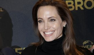 """FILE - In this Nov. 27, 2014 file photo, director Angelina Jolie poses for photographers during a photo call for her film """"Unbroken"""" in Berlin, Germany. The film did not receive any Golden Globe nominations on Thursday.  (AP Photo/Michael Sohn, File)"""