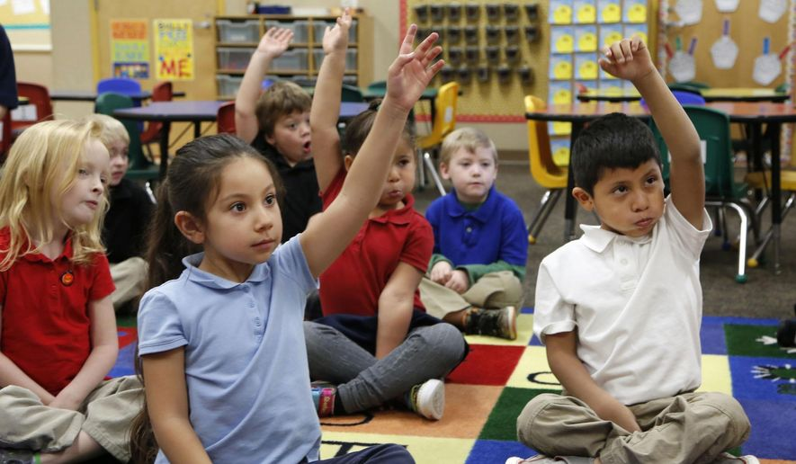 Ella Perez, left, and Christian Sliva-Pedroz raise their hands to answer a question as student teacher Josh Wieder reads to the students in Bethany Farrell's kindergarten class on Nov. 5, 2014, at Miller Elementary School in Lafayette, Ind. (AP Photo/Journal & Courier, John Terhune) ** FILE **
