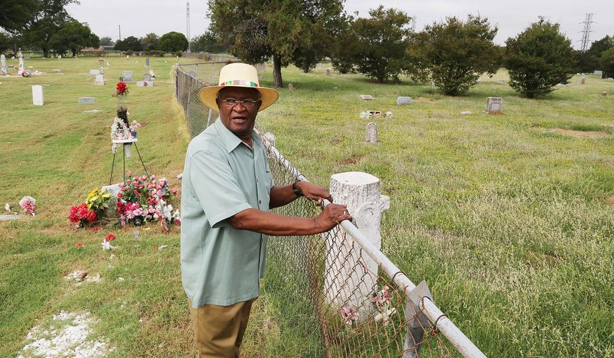 In this Sept. 1, 2014 photo, Noah Jackson stands at a fence line at Greenwood cemetery in Waco, Texas.  On one side are more than 1,000 black residents, including college presidents, business leaders, a state legislator, a baseball star and Broadway baritone Jules Bledsoe are buried.  Soon the fence, a rusting legacy of Jim Crow segregation, is likely to become history. The city of Waco, which has maintained the black side of Greenwood since 2007, has informally agreed to take over maintenance of the white side from the East Waco Greenwood Cemetery Association in the coming year. The city intends to remove the separating fence and unify the entire cemetery within a new fence.   (AP Photo/Waco Tribune Herald, Rod Aydelotte)