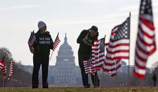 With the Capitol in the background, Army veteran David Dickerson of Oklahoma City, Okla., right, and Air Force veteran Linda Stanley, from San Diego, Calif., now with Iraq and Afghanistan Veterans of America (IAVA), join others to place 1,892 flags representing veteran and service members who have died by suicide to date in 2014, Thursday, March 27, 2014, on the National Mall in Washington. The event also marked the introduction of The Suicide Prevention for America's Veterans Act by Sen. John Walsh, D-Mont., which calls for greater access to mental health care. (AP Photo/Charles Dharapak) **FILE**