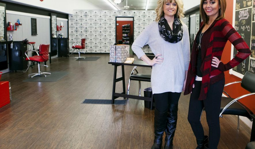 In this Nov. 13, 2014 photo, Nicole Snell, left, and Tyler Stickle pose inside the Cutting Edge salon they opened in July in downtown Galesburg, Ill. Snell and Stickle decided to become independent after working for JCPenney salon for the past few years.(AP Photo/The Register-Mail, Steve Davis)