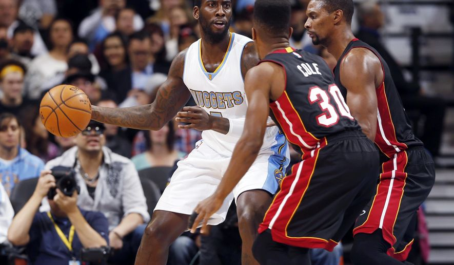 Denver Nuggets forward J.J. Hickson, left, looks to pass the ball under defensive pressure from Miami Heat guard Norris Cole, front right, and center Chris Bosh in the first quarter of an NBA basketball game in Denver on Wednesday, Dec. 10, 2014. (AP Photo/David Zalubowski)