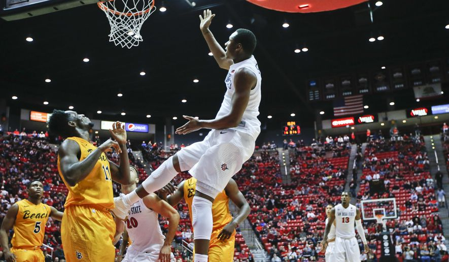 San Diego State forward Skylar Spencer scores on a reverse layup after beating Long Beach State forward David Samuels with a baseline drive during the first half of an NCAA college basketball game Wednesday, Dec. 10, 2014, in San Diego. (AP Photo/Lenny Ignelzi)