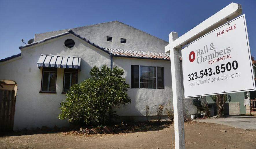 FILE - In this Oct. 27, 2014 file photo, a realty sign hangs in front of a home for sale in Los Angeles. Freddie Mac reports on average U.S. mortgage rates for this week on Thursday, Dec. 11, 2014. (AP Photo/Nick Ut, File)