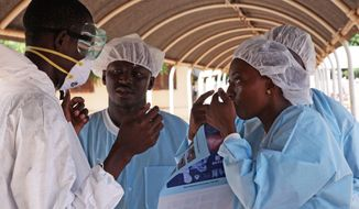 In this file photo taken Saturday, Oct. 25, 2014, a health worker, right, briefs another, left, on the use of their Ebola security gear before working with diseased Fanta Kone at a Ebola virus center in  Kayes, Mali. The last Ebola patient being treated in Mali has survived the disease and been released, the Health Ministry said Friday, Dec. 12, 2014. (AP Photo/Baba Ahmed, File)