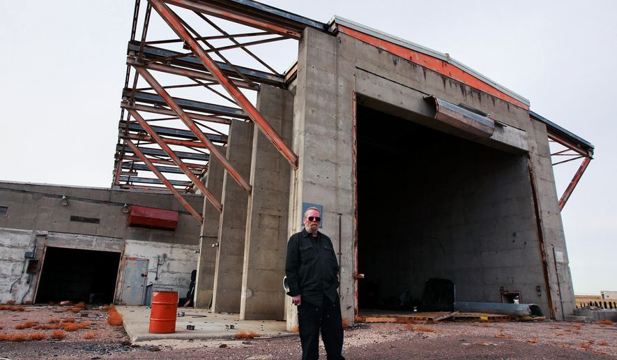 In this Thursday, Dec. 4, 2014, photo, Craig Johnson stands outside the launch buildings that once housed Atlas D intercontinental ballistic missiles at the former Atlas Missile Site No. 3 east of Cheyenne, Wyo. For nearly 13 years, the U.S. Army Corps of Engineers and the Wyoming Department of Environmental Quality have worked to clean groundwater contamination caused by the improper drainage of trichloroethylene.  (AP Photo/The Casper Star-Tribune, Alan Rogers)