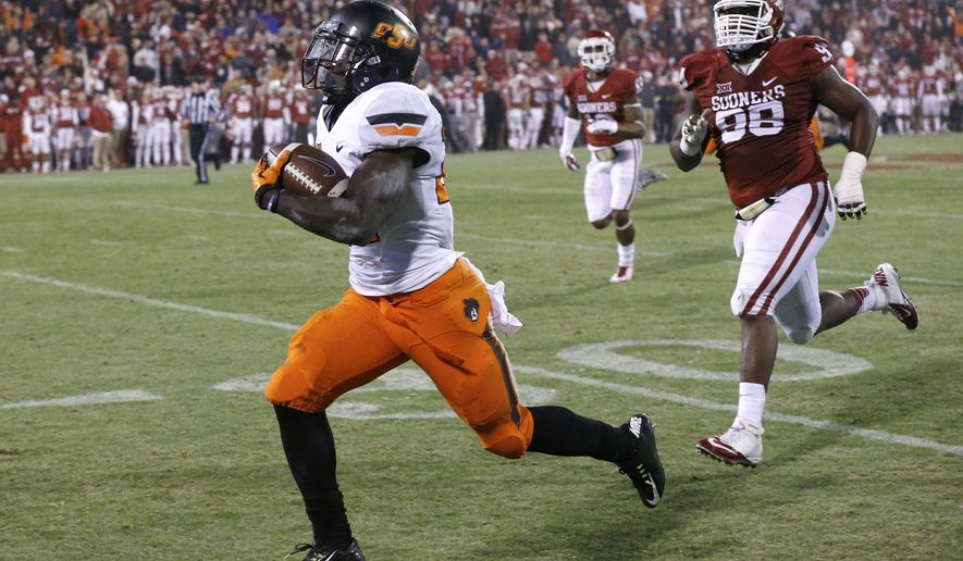 FILE - In this Dec. 6, 2014 file photo Oklahoma State wide receiver Tyreek Hill, left, is chased by Oklahoma defensive tackle Chuka Ndulue (98) runs a punt return in to tie the game in the fourth quarter of an NCAA college football game in Norman, Okla. Hill was arrested Thursday, Dec. 11, 2014, accused of punching and choking his girlfriend. (AP Photo/Sue Ogrocki, File)