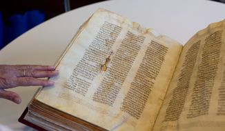 In this Oct. 5, 2014 file photo, a library official shows a Jewish manuscript smuggled into Israel from Damascus in a Mossad spy operation in the early 1990s, in Jerusalem. The manuscript is one of the earliest existing complete manuscripts of the Hebrew bible. Two decades after Israeli spies helped whisk eight ancient Hebrew bibles from Damascus to Jerusalem, Israel's national library asked an Israeli court Monday, Dec. 8, 2014 to grant it official custodianship over the manuscripts, a move that is liable to spark a bitter ownership battle over the some of the Syrian Jewish community's most important treasures. (AP Photo/Sebastian Scheiner, File)