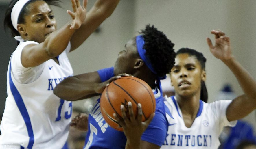 Middle Tennessee's Shanice Cason, middle, looks for an opening between Kentucky's Bria Goss, left, and Janee Thompson (3) during the first half of an NCAA college basketball game, Friday, Dec. 12, 2014. (AP Photo/James Crisp)