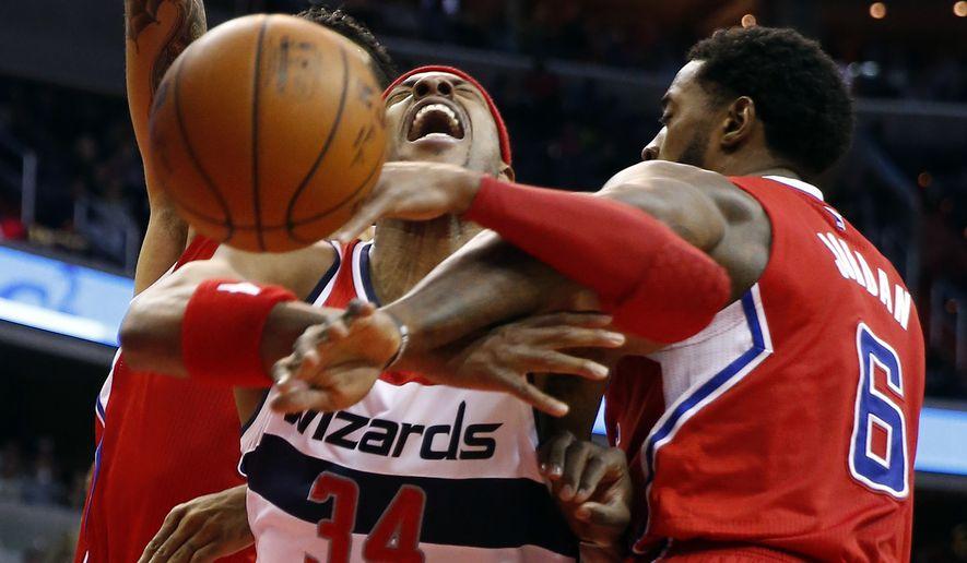 Los Angeles Clippers forward Matt Barnes (22) and center DeAndre Jordan (6) combine on Washington Wizards forward Paul Pierce (34) in the second half of an NBA basketball game, Friday, Dec. 12, 2014, in Washington. The Wizards won 104-96. (AP Photo/Alex Brandon)