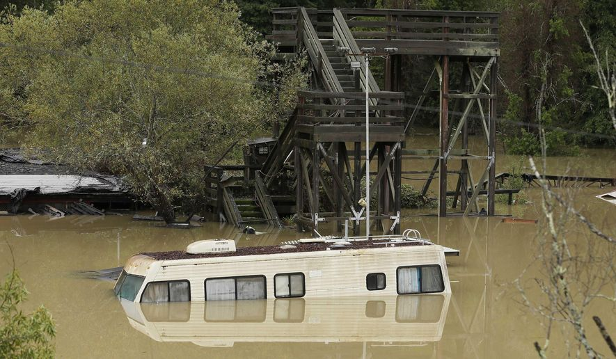 An RV sits underwater from the flooded  Russian River Friday, Dec. 12, 2014, in Guerneville, Calif.   While the sun rose Friday in a dry San Francisco sky, the storm's affects lingered in Northern California. In Sonoma County, the Russian River was approaching flood stage and was expected to crest several feet above it by early afternoon. Officials advised residents of about 300 homes to evacuate low-lying areas. (AP Photo/Eric Risberg)