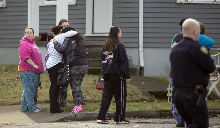 Family members greet their children who were escorted out of Rosemary Anderson High School in North Portland after a shooting on Dec. 12, 2014. A shooter wounded two boys and a girl outside a U.S. high school Friday in what is believed to be a gang-related attack, police said. (AP Photo/The Oregonian, Kristyna Wentz-Graff)
