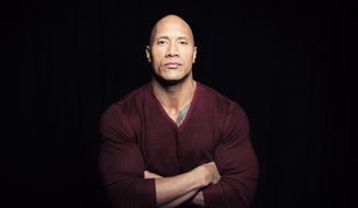 """In this Dec. 8, 2014, photo, Dwayne """"The Rock"""" Johnson poses in New York to promote his TNT reality series """"Wake Up Call,"""" premiering Friday at 9 p.m. ET. (Photo by Taylor Jewell/Invision/AP) ** FILE **"""