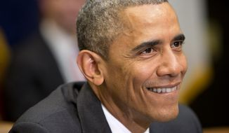 President Barack Obama smiles after being asked by a member of the media about his sore throat, during a meeting with his national security and public health teams about the Ebola response, Friday, Dec. 12, 2014, in the Roosevelt Room of the White House in Washington. (AP Photo/Jacquelyn Martin)
