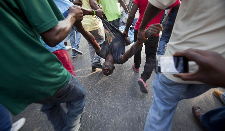 Anti-government protesters carry the body of a demonstrator who was shot to death during clashes with the National Police in Port-au-Prince, Haiti, Saturday, Dec. 13, 2014. Haiti's capital has endured a growing number of violent demonstrations in which protesters are demanding long-delayed elections and the resignations of Prime Minister Laurent Lamothe as well as President Michel Martelly. The protests also spread to other towns, including Gonaives and Cap-Haitien. (AP Photo/Dieu Nalio Chery)
